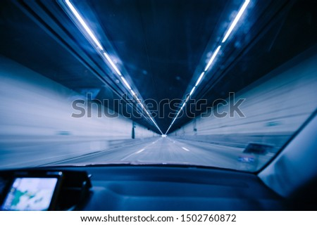 Perspective view fron the car at the long blue tunnel with end at the end Stockfoto ©