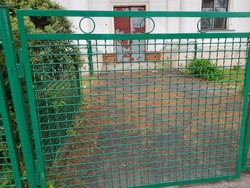 Perspective view of a green chain link fence as seamless background with strong geometric patterns, tones and texture
