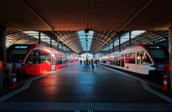 Perspective view of a platform in Lucerne Central Railway Station with sunlight cast on trains parking by the platform & passengers hurrying for boarding~A beautiful corner in Lucern Railroad Terminal