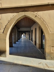 Perspective view of a set of medieval arcades.  Personal point of view between sunbeams and shadows.  Color background image.
