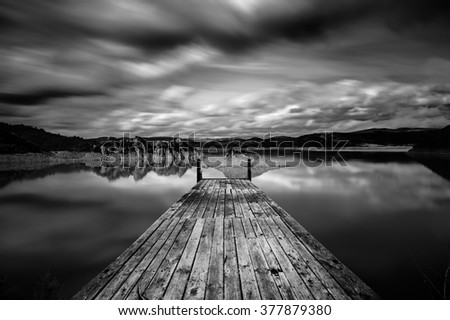 Perspective view of a wooden pier in a completely calm lake with reflections of the sky - long exposure