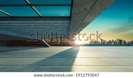 Perspective view of empty concrete floor and modern rooftop building with sunset cityscape scene. Mixed media