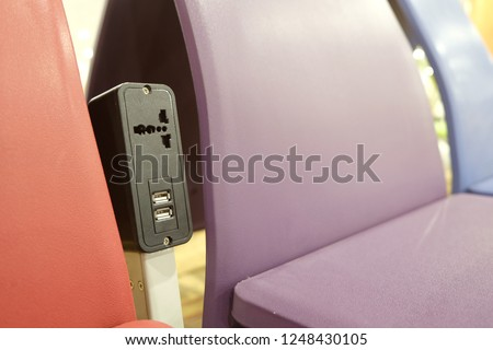 Perspective view of traditional power outlet and USB chargers between colorful modern chairs #1248430105
