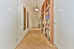 Perspective view of white apartment corridor with parquet floor and wooden bookcases with books under glowing lamps