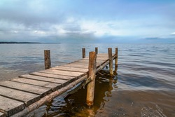 Perspective view of wooden pier at lake. Small bridge in water