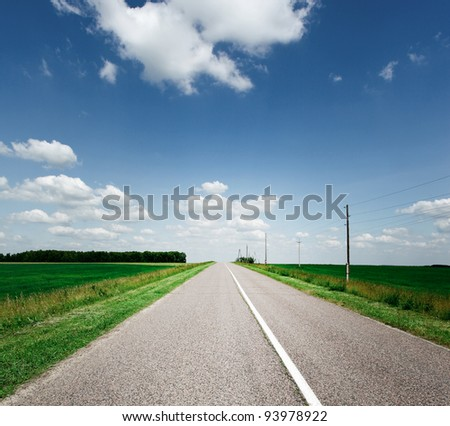 perspective view to long asphalt road over fields