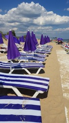 Perspective view to row of striped chaise-longues and purple closed parasols on clear beach sand with wood flooring path along. Amazing cloudscape above summer beach. Sunny day at seaside.