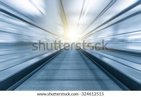 Perspective wide angle black and white view of modern light blue illuminated and spacious high-speed moving escalator with fast blurred trail of handrail in vanishing traffic motion #324612515