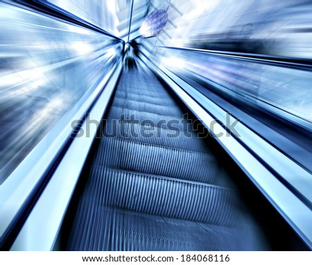 Perspective wide angle view of modern metal chrome and light blue illuminated airport, spacious high-speed technology moving escalator, fast blurred trail of steel handrail in vanishing traffic motion
