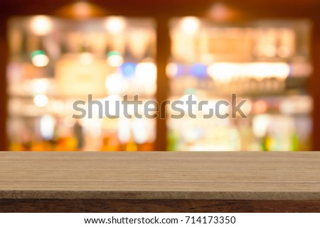 Perspective wooden table on top over blur  wine bar in cafe background, can be used mock up for montage products display or design layout.