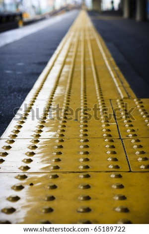 Perspective yellow tactile strip for cane or foot of blind person, Japan