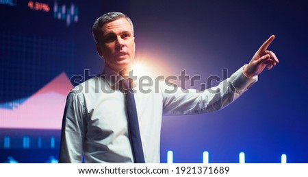 Persuasive mature man gesticulating and talking about financial charts from stage during business seminar Foto stock ©