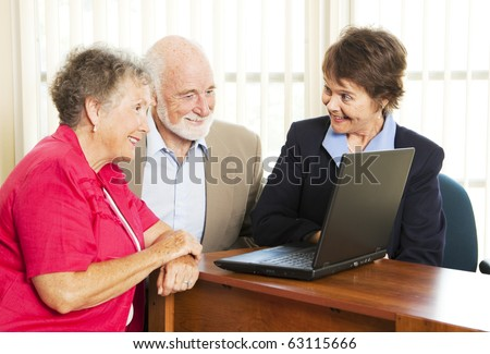 Persuasive sales woman pitches financial services to an elderly couple.