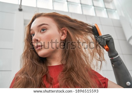 Perturb pretty woman with hand implant looking at damaged hair tips and worries about split hair, while brushing her ginger hair at home. Stock photo Photo stock ©