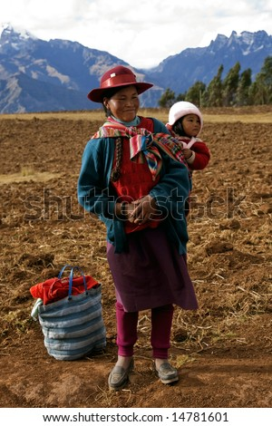 PERU - AUGUST 1: A native Peruvian woman demonstrates how to wrap and carry a child August 1, 2007 in Sacred Valley, Peru. - stock photo