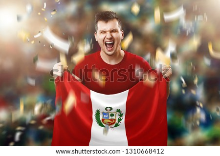 Peru is a fan, a fan of a man holding Peru's national flag in his hands. Soccer fan in the stadium.
