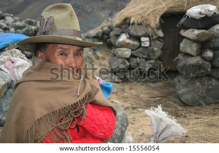 PERU - SEPTEMBER 23: Old indigenous woman in traditional clothes posing in front of a poor stone house. Great trekking adventure September 23, 2005 in Peru. - stock photo