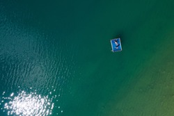 Peruca Lake. Floating platform with a sun tanning couple aerial top view. Bright sn reflecting in green lake waves. Dalmatia, Croatia