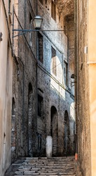 Perugia, Italy city in Umbria vertical view on stairs steps in narrow alley with sunlight in dark street road stone architecture