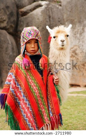 Peruvian boy in traditional dress with lama at ancient ruins in Cusco, Peru. - stock photo