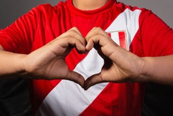 Peruvian boy making a heart with his hands and in the background the Peruvian shirt