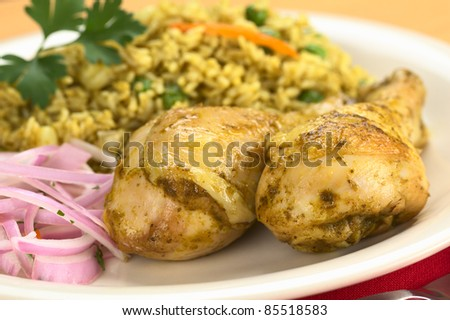 Peruvian dish called Arroz con Pollo (Rice with Chicken) made of rice, peas, corn, aji (hot pepper) and cilantro, served with Salsa Criolla (onion salad) (Selective Focus, Focus on the front)