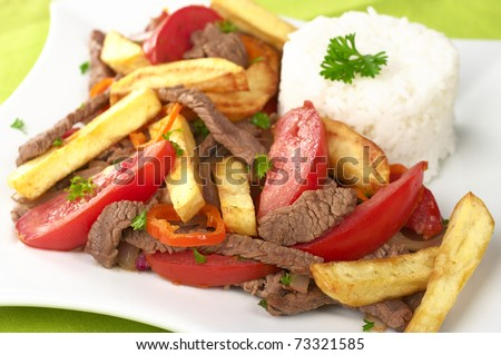 Peruvian dish called Lomo Saltado made of tomato, beef meat and onions mixed with French fries and served with rice (Selective Focus, Focus on the front)