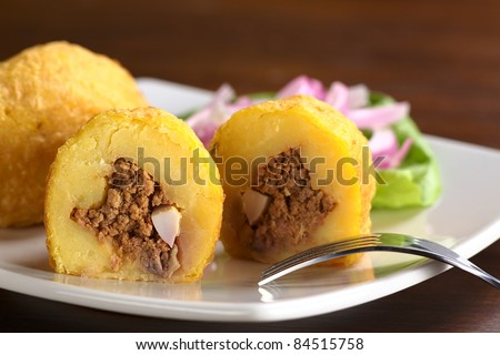 Peruvian dish called Papa Rellena (Stuffed Potato) made of mashed potatoes and filled with meat and egg (Selective Focus, Focus on the front of the half papa rellena)