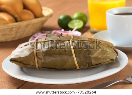 Peruvian food called Tamal which is prepared from cooked corn mixed with chicken and wrapped in banana leaves. It is eaten for breakfast or as appetizer at lunch (Selective Focus, Focus on the front)