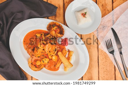 Peruvian food: Peruvian Dish a lo macho fish, wooden table, served on a white plate, (Fish fried in seafood sauce, accompanied by potato sea bream and rice) Foto d'archivio ©