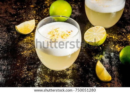 Peruvian, Mexican, Chilean traditional drink pisco sour liqueur, with fresh lime, on rusty black table, copy space #750051280