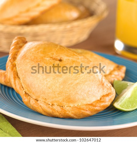 Peruvian snack called Empanada (pie) filled with chicken and beef meat on blue plate with limes (Selective Focus, Focus on the middle front part of the empanada)