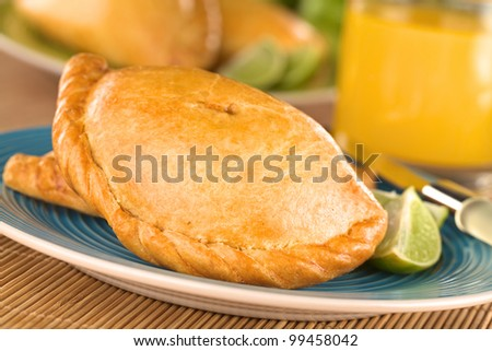 Peruvian snack called Empanada (pie) filled with chicken and beef served with limes (Selective Focus, Focus on the middle front part of the empanada)