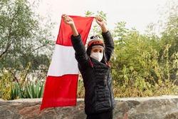Peruvian woman wearing a chullo and mask raising the flag of Peru