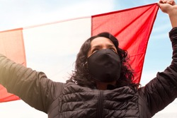 Peruvian woman with mask holds the Peruvian flag with her hands up