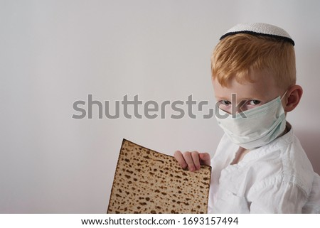 Pesach and Coronavirus epidemic. Child in medical mask and matzah for Pesach.