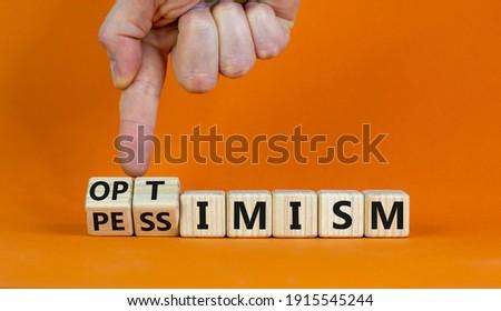 Pessimism or optimism symbol. Businessman turns cubes and changes the word 'pessimism' to 'optimism'. Beautiful orange table, orange background. Business and optimism or pessimism concept. Copy space. Stockfoto ©