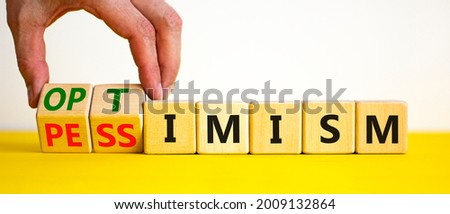 Pessimism or optimism symbol. Businessman turns cubes and changes the word 'pessimism' to 'optimism'. Beautiful yellow table, white background. Business, optimism or pessimism concept. Copy space. Foto stock ©