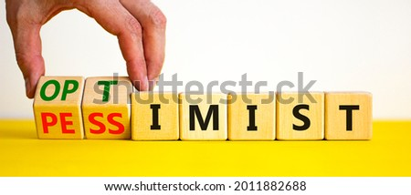Pessimist or optimist symbol. Businessman turns cubes and changes the word 'pessimist' to 'optimist'. Beautiful yellow table, white background. Business, optimist or pessimist concept. Copy space. Foto stock ©