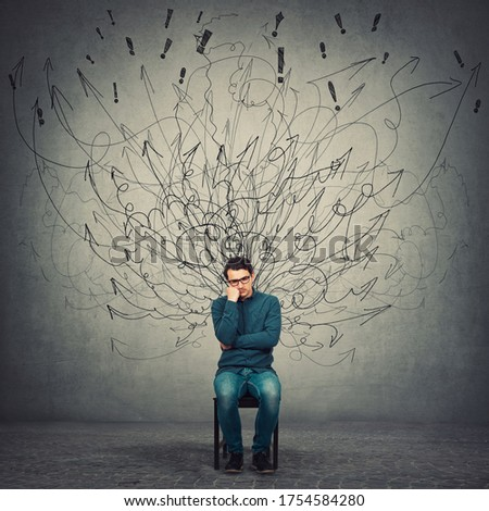 Pessimistic, disappointed and depressed businessman keeps hand under cheek, seated on a chair as mess curves comes out of him like negative energy. Dissatisfied person suffers a midlife crisis. Foto stock ©