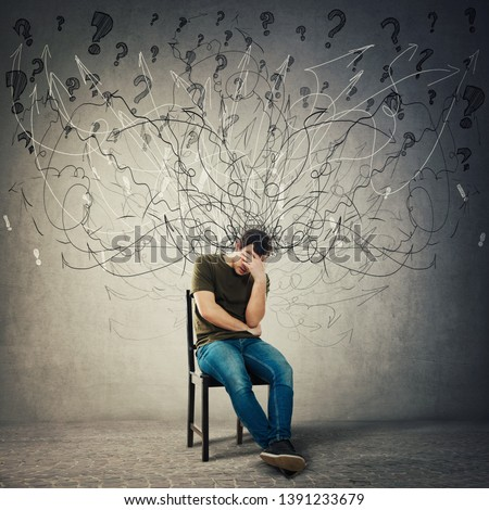 Pessimistic, disappointed man sitting on a chair in a dark room covering face with hand. Desperate guy seated alone suffer anxiety, distress depression feeling. Mess go out of head, losing memory.