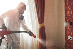 Pest control specialist in white hazmat contractor working in flat and hotel.