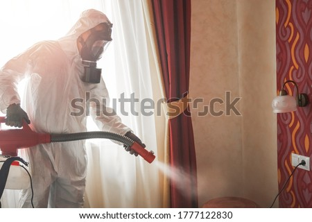 Pest control specialist in white hazmat contractor working in flat and hotel. Foto d'archivio ©