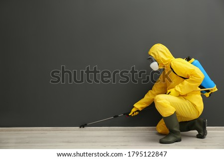 Pest control worker in protective suit spraying pesticide near black wall indoors. Space for text Foto d'archivio ©