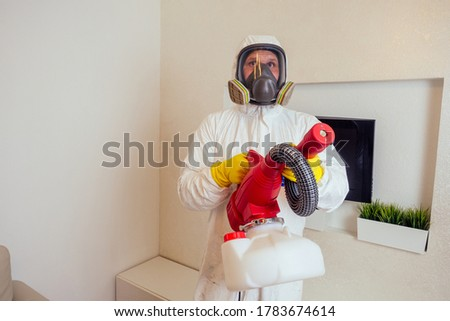 pest control worker in uniform spraying pesticides under couch in living lounge room Foto stock ©