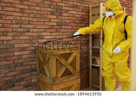 Pest control worker spraying pesticide on wooden crate indoors Foto stock ©