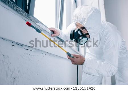pest control worker spraying pesticides under windowsill at home #1135151426