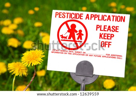 Pesticide Application sign with dandelions in the background