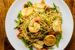 Pesto Pasta with jumbo shrimp and pesto sauce (extra virgin olive oil, pine nuts and basil), mixed with fresh chopped asparagus and halved cherry tomatoes served over homemade pasta & seasoned w/ s&p.