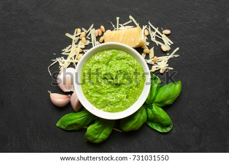 Pesto sauce in a bowl with pine nuts, parmesan and garlic over black stone background. top view